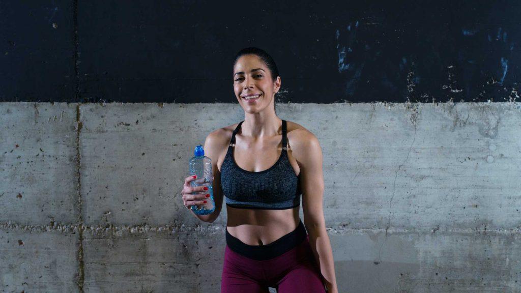 Hacer ejercicio con dos botellas y beber agua
